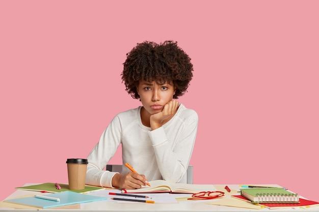 분홍색 벽에 책상에 포즈 슬픈 스트레스가 많은 학생 소녀