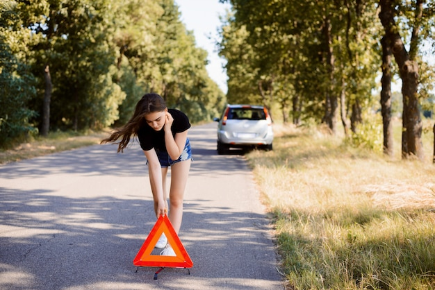 Sad student girl putting red emergency triangle stop sign because her car has broken in the countryside