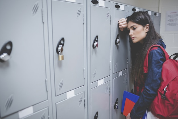 Sad student leaning on locker at university