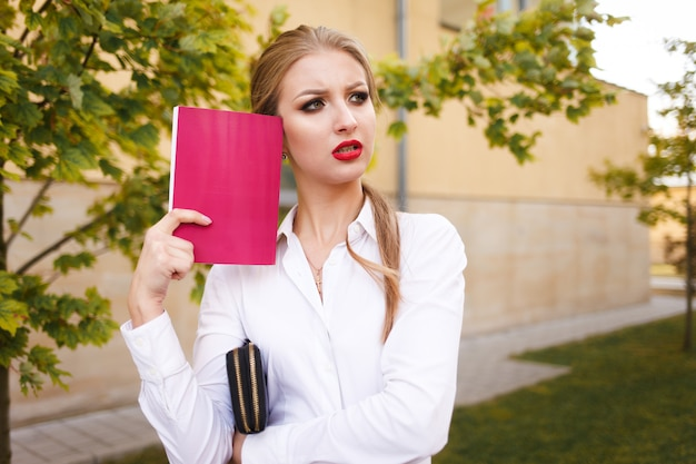 Sad student with a book in her hands thinks about exams. young business lady think about problem on work