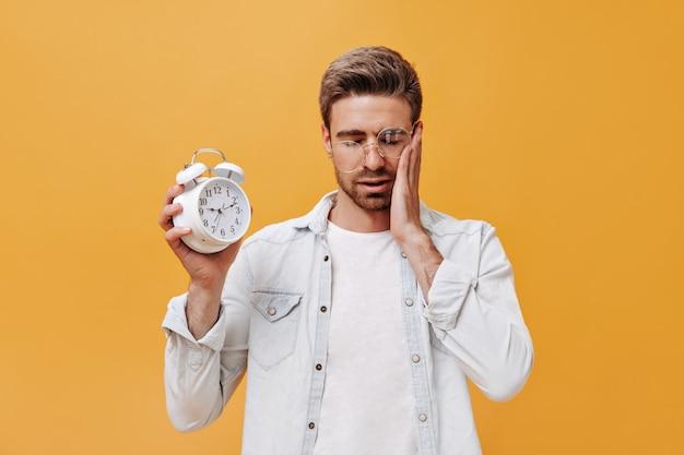 둥근 안경, 흰색 현대 셔츠 및 멋진 티셔츠에 슬픈 세련된 남자가 닫힌 눈으로 포즈를 취하고 큰 알람 시계를 들고