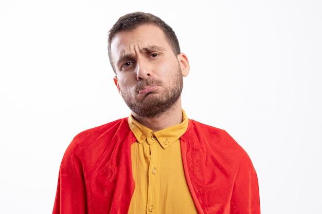 L'uomo triste del supereroe con il mantello rosso esamina la parte anteriore isolata sulla parete bianca