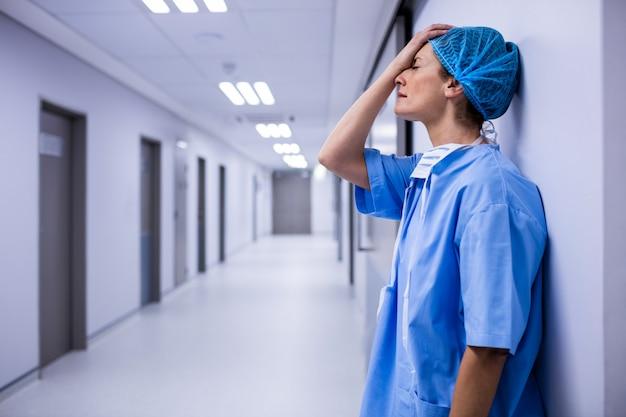 廊下の壁にもたれて悲しい外科医
