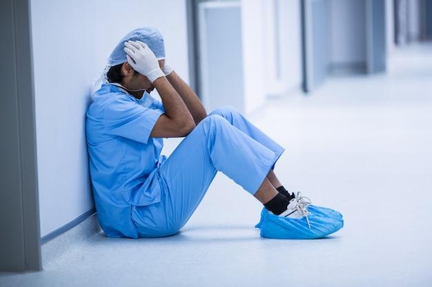 床に座って悲しい外科医