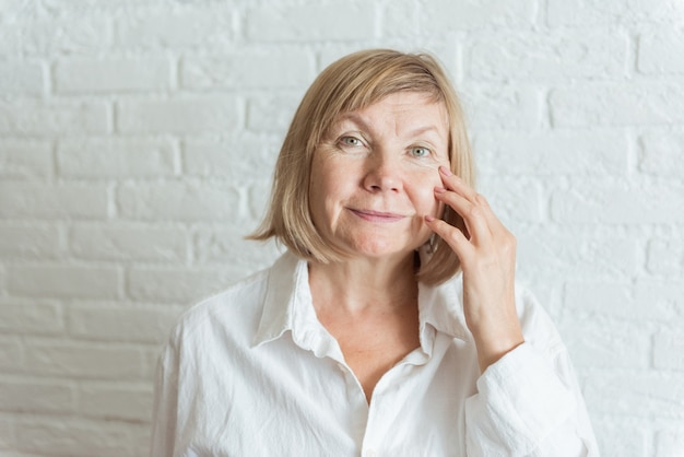 Sad surprised old mature woman looking at camera worried about facial wrinkles