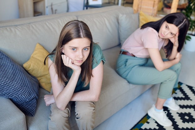 Sad teenage girl being in conflict with mother sitting on sofa and looking away, family misunderstanding concept