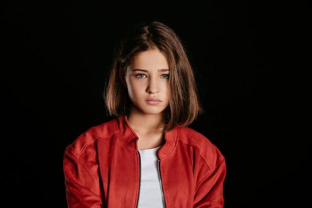 Sad teenage girl on dark