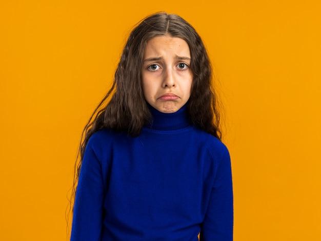 オレンジ色の壁に分離された悲しい10代の少女