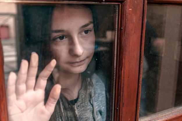 寒い秋の日に窓を見ている悲しい十代の少女