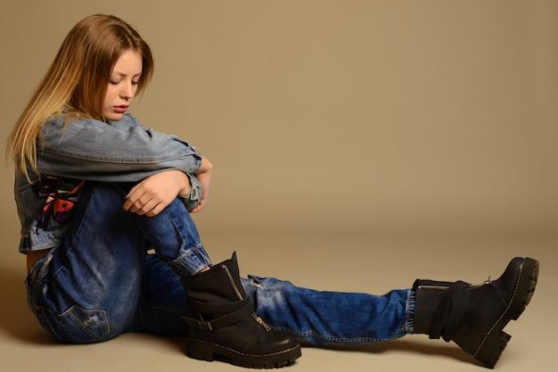 Грустная девочка-подросток сидит на полу в джинсовой куртке