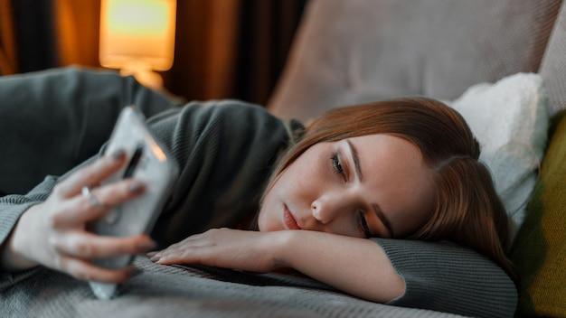 불면증 인터넷 서핑이나 침대에 누워 밤에 스마트 폰을 사용하여 채팅으로 고통받는 슬픈 십 대 소녀. 우울증 인터넷 중독과 젊은 여성의 우울증. 긴 웹 배너.