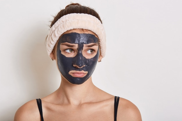 Грустная женщина-подросток с маской для лица смотрит в сторону, выражает печаль, носит футболку без рукавов и повязку для волос