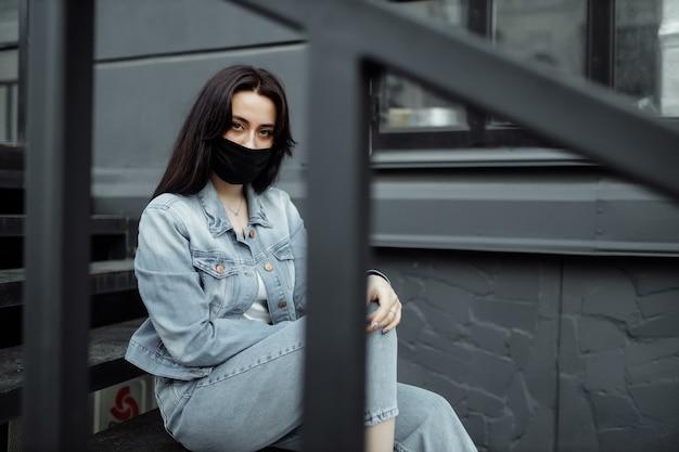 Sad teenager girl in medical mask behind bars schools