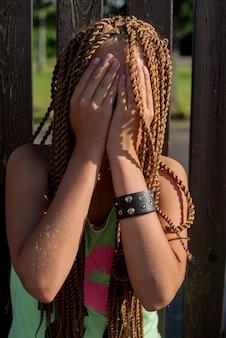 긴 땋은 머리를 가진 슬픈 십대 소녀가 손으로 덮인 나무 울타리에 서 있다 프리미엄 사진