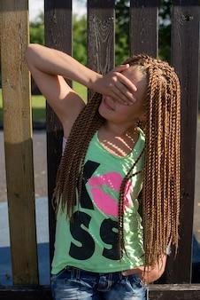 긴 땋은 머리를 가진 슬픈 십대 소녀가 손으로 덮인 나무 울타리에 서 있다