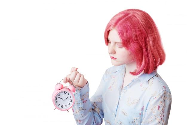 Грустная девушка-подросток с розовыми волосами держит будильник на белом