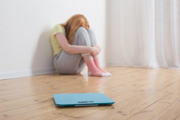 木製の床にスケールを持つ悲しいティーンエイジャーの女の子
