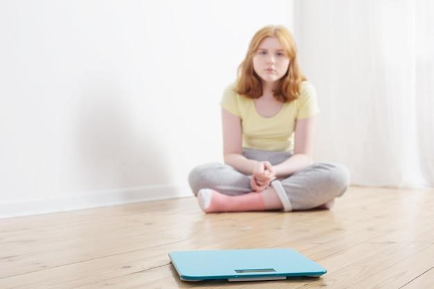 Грустная девочка-подросток с весами на деревянном полу