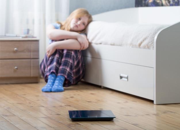 Грустная девочка-подросток с весами на полу