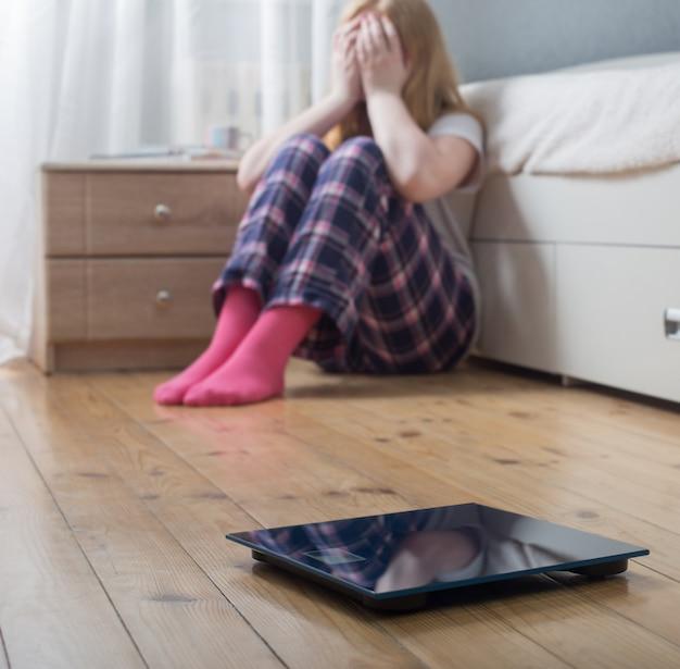 床のスケールを持つ悲しいティーンエイジャーの女の子