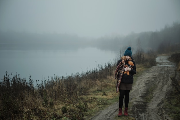 Sad teenager woman hugging teddy bear by foggy lake. concept of adolescence and adolescent problems.