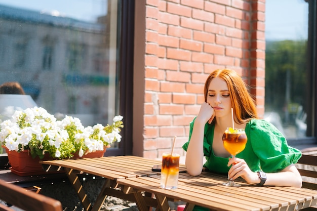 Sad thoughtful young woman drinking cocktail through straw sitting at table in outdoor cafe in sunny summer day. beautiful female hipster student drinking cool lemonade through straw.