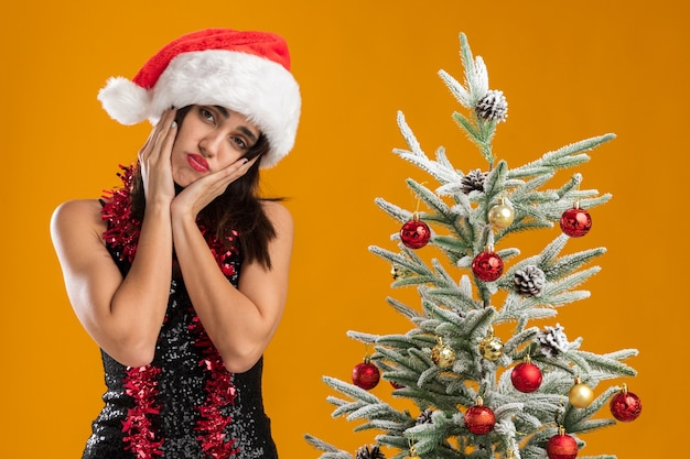 Testa di inclinazione triste giovane bella ragazza che indossa il cappello di natale con la ghirlanda sul collo in piedi vicino all'albero di natale che mette le mani sulle guance isolate sul muro arancione