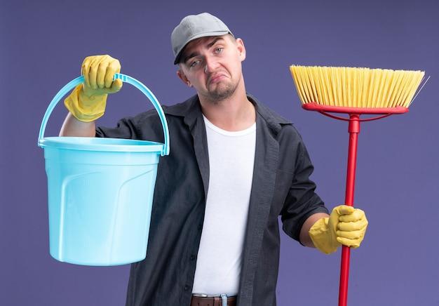Testa di inclinazione triste giovane bel ragazzo delle pulizie che indossa t-shirt e berretto con glaves che tiene secchio con mop isolato sulla parete viola