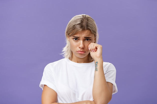 Sad and timid  woman looking from under forehead holding fist near eye as if whiping teardrop being upset