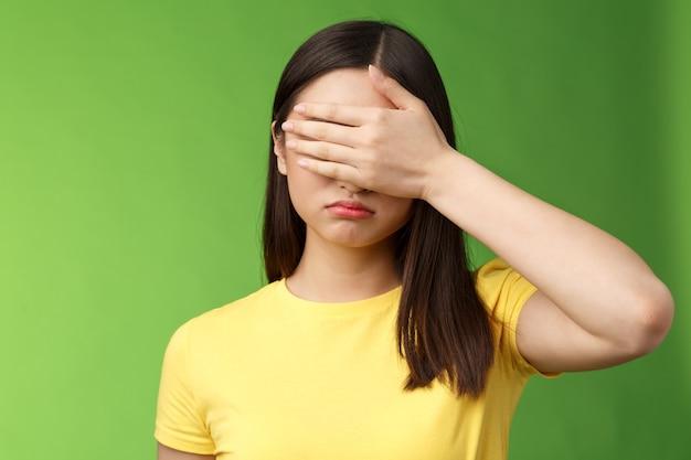 Грустная усталая азиатская девушка темная стрижка, закрытые глаза держат взгляд, гримасничаются, чувствуя себя мрачным и расстроенным, стоят на зеленом фоне в депрессии, не желая смотреть, как рушится жизнь, позируют желтую футболку.