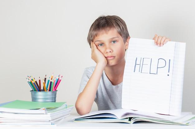 宿題をして、単語ヘルプでノートを保持している悲しい疲れた少年