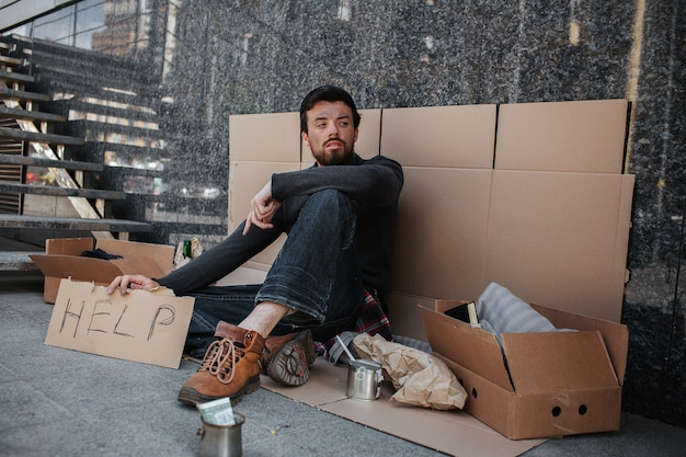 Sad and tired dark-haired man is sitting on the cardboard and holding another cardboard with the word help writing on it. he is looking aside. he is homeless.