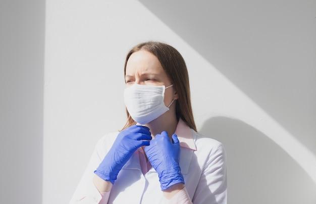 창에서 자연광으로 생각에 파란색 의료 장갑을 끼고 슬픈 피곤한 여의사