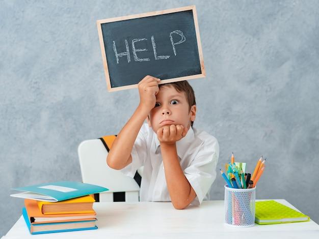 Грустный усталый разочарованный мальчик-школьник за столом и держит бумагу со словом help. трудности обучения, концепция образования