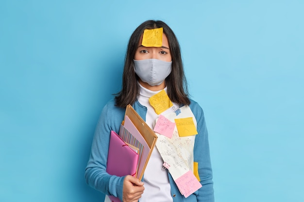 Sad tired student with dark hair has stickers on clothes and forehead going to pass exam during pandemic virus spread.