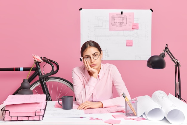 Sad tired woman wears spectacles poses at desktop works all day long on blueprints involved in learning process