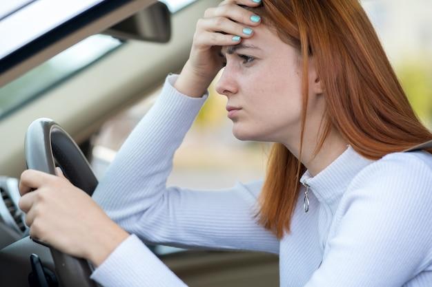 교통 체증에 자동차 스티어링 휠 뒤에 앉아 슬픈 피곤 된 캔디 여자 드라이버.