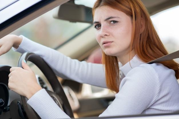 자동차 스티어링 휠 뒤에 앉아 슬픈 피곤 된 yound 여자 드라이버