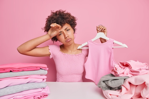 Sad tired young housewife sortes clothes for laundry holds pink shirt on hanger wipes forehead from tiredness sits at table with two stacks of clothing chooses something unnecessary for donation