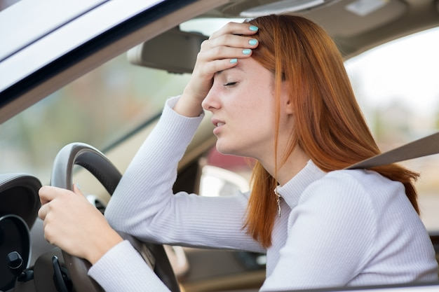 Sad tired young woman driver sitting behind the car steering wheel in traffic jam