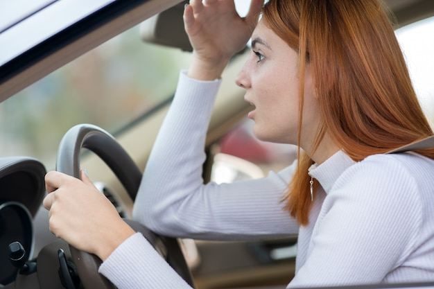 Sad tired young woman driver sitting behind the car steering wheel in traffic