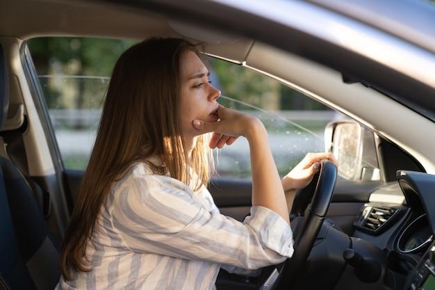 슬프고 피곤한 젊은 여성이 차를 운전하는 불행한 소녀 운전자가 우울하고 불안한 핸들을 잡고 있다