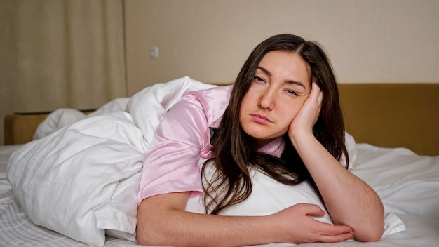 Sad unhappy dark haired woman in pink pajama sighs deeply lying lonely on king size bed with clean white linen in bedroom close view