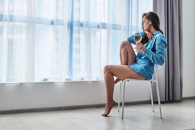 Грустная несчастная подавленная грустная задумчивая одинокая пьющая женщина с бокалом белого вина, страдающая от алкоголизма, сидит одна дома у окна во время жизненных проблем и депрессии