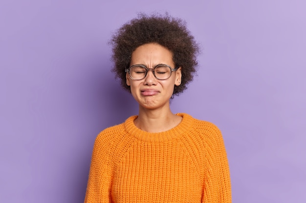 곱슬 머리를 가진 슬픈 불행한 여성 십대는 좌절감을 느끼고 실망하고 투명한 안경 오렌지 니트 스웨터를 입습니다.