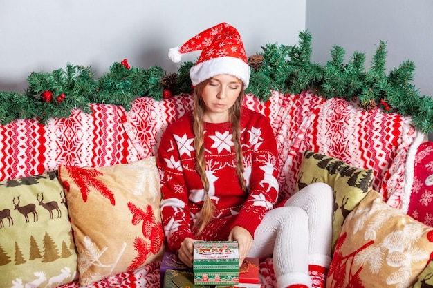 Sad unhappy girl in santa hat opens christmas gift boxes in new year decorations