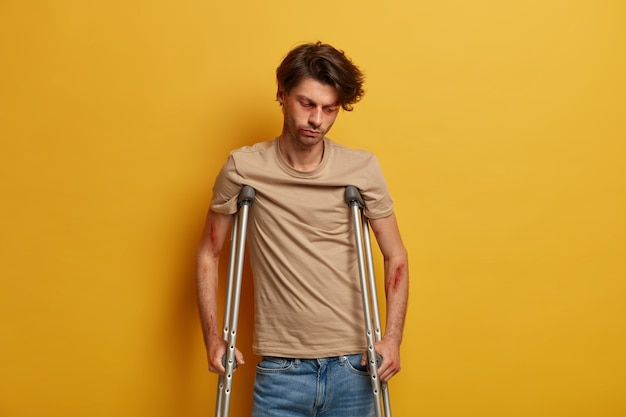Sad unhappy man looks down, has serious injury after falling down from height, tired of long recovery period, tries to walk with crutches, poses against yellow wall. handicapped disabled male
