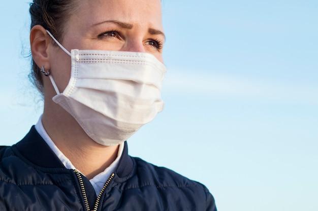 悲しい不幸な物思いにふける欲求不満少女、空を背景にコロナウイルスに対する彼女の顔に医療用防護マスクの若い動揺の絶望的な女性。ウイルス、うつ病、流行、ドラマのコンセプト、コピースペース