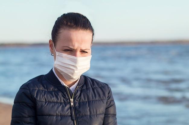 悲しい不幸な物思いにふける欲求不満少女、ビーチの海の上を歩くコロナウイルスに対する彼女の顔に医療用防護マスクの若い動揺の絶望的な女性。ウイルス、うつ病、隔離、流行、ドラマのコンセプト