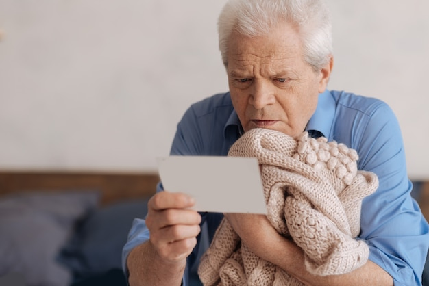 Sad unhappy senior man holding his wifes knitted jacked and reading a note while having nostalgic memories